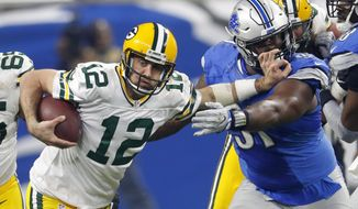 Green Bay Packers quarterback Aaron Rodgers (12) stiff arms Detroit Lions defensive tackle A'Shawn Robinson (91) during the second half of an NFL football game, Sunday, Jan. 1, 2017, in Detroit. (AP Photo/Paul Sancya)