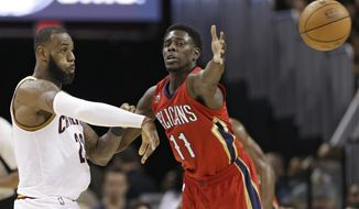 Cleveland Cavaliers' LeBron James, left, passes against New Orleans Pelicans' Jrue Holiday in the second half of an NBA basketball game, Monday, Jan. 2, 2017, in Cleveland. The Cavaliers won 90-82. (AP Photo/Tony Dejak)