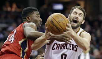New Orleans Pelicans' Solomon Hill, left, knocks the ball loose from Cleveland Cavaliers' Kevin Love in the first half of an NBA basketball game, Monday, Jan. 2, 2017, in Cleveland. (AP Photo/Tony Dejak)