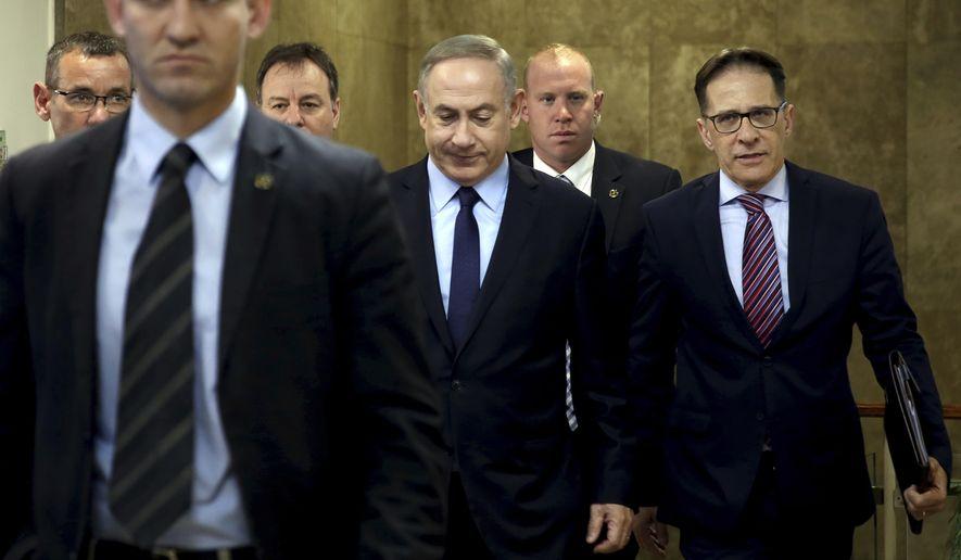 Israeli Prime Minister Benjamin Netanyahu (center) arrives for a weekly cabinet meeting, in Jerusalem, Sunday, Jan. 1, 2017. (Gali Tibbon/Pool photo via AP)