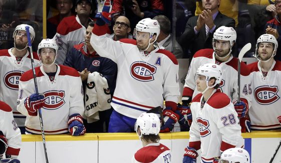 Montreal Canadiens defenseman Shea Weber, center, acknowledges the applause as a tribute to him is played on the scoreboard during the first period of an NHL hockey game between the Canadiens and the Nashville Predators Tuesday, Jan. 3, 2017, in Nashville, Tenn. Weber was the captain of the Predators before being traded to the Canadiens for defenseman P. K. Subban during the off-season. (AP Photo/Mark Humphrey)