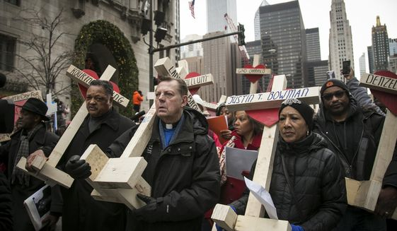 The Rev. Jesse Jackson (left), the Rev. Michael Pfleger and Illinois state Sen. Jacqueline Collins led a Dec. 31 march down Michigan Avenue in Chicago to remember the hundreds of people killed by violence in the city last year. (Associated Press/File)
