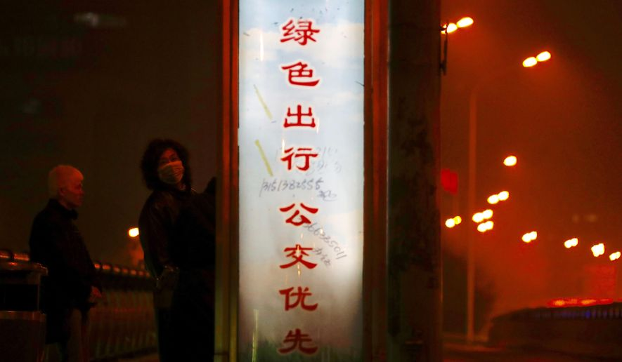 """A pedestrian wearing a mask looks back while passing by a slogan that reads: """"If you want to go out, please take a public bus"""" in Beijing Monday, Jan. 2, 2017. Beijing and other cities across northern and central China were shrouded in thick smog Monday, Jan. 2, 2017, prompting authorities to delay dozens of flights and close highways. (AP Photo/Andy Wong)"""