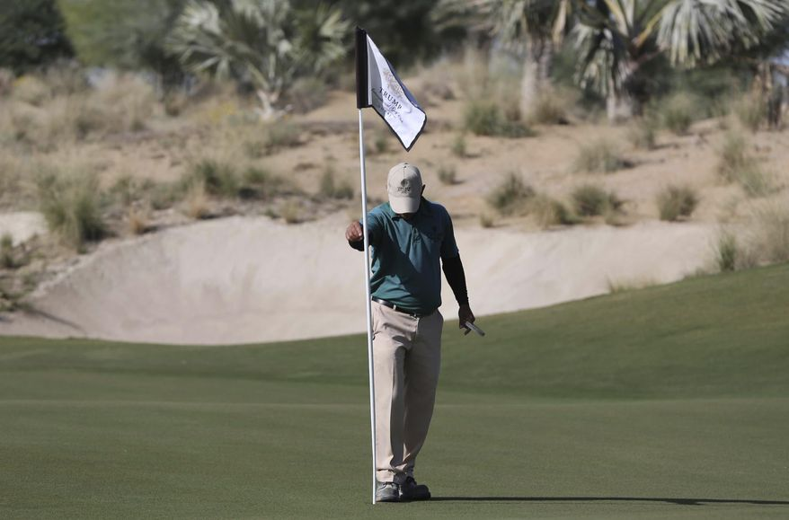 In this Tuesday, Dec. 20, 2016 photo, an employee fixes a flag post on the green at the Trump International Golf Club, in Dubai, United Arab Emirates. The 18-hole golf course in Dubai bearing Donald Trump's name exemplifies the questions surrounding his international business interests. The course will open in February 2017 in the United Arab Emirates, but concerns about security, financial agreements and other matters have yet to be answered by the incoming 45th American president.(AP Photo/Kamran Jebreili)