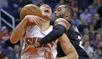 Phoenix Suns guard Devin Booker, left, gets fouled by Miami Heat guard Wayne Ellington as Booker goes up for a shot during the first half of an NBA basketball game Tuesday, Jan. 3, 2017, in Phoenix. (AP Photo/Ross D. Franklin)