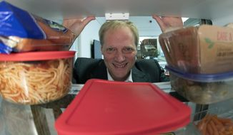 In this Tuesday, Dec. 6, 2016 photo, Brian Wansink, a food behavior scientist at Cornell University, poses for a photo in a food lab at the university in Ithaca, N.Y. Wansink says even though it shortens shelf life, move fruits and vegetables out of crisper drawers and put them at eye level. Keep good foods in clear bags or containers and less healthy things like leftover pizza in aluminum foil. In one study, people who put fruits and vegetables on the top shelf ate nearly three times more of them than they did the week before. (AP Photo/Mike Groll)