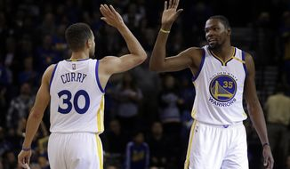Golden State Warriors' Stephen Curry (30) and Kevin Durant, right, celebrate in the final minutes of an NBA basketball game against the Denver Nuggets on Monday, Jan. 2, 2017, in Oakland, Calif. Golden State won 127-119. (AP Photo/Ben Margot)