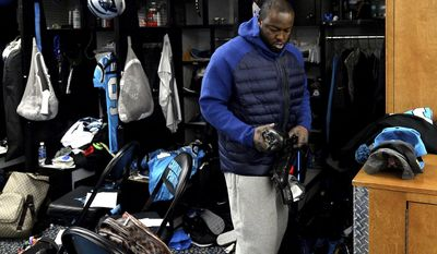 Carolina Panthers defensive end Charles Johnson looks at a pair of his cleats as he cleans out his locker at Bank of America Stadium on Monday, Jan. 2, 2017, in Charlotte, N.C. (Jeff Siner/The Charlotte Observer via AP)