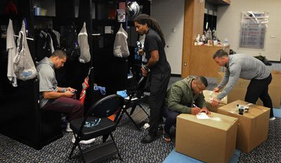 Carolina Panthers safety Kurt Coleman, left, sits in his locker as safety Tre Boston, center, passes by while team personnel, right, label boxes of player items to be shipped at Bank of America Stadium on Monday, Jan. 2, 2017, in Charlotte, N.C. (Jeff Siner/The Charlotte Observer via AP)