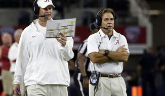 FILE - In this Sept. 5, 2015, file photo, Alabama head coach Nick Saban, right, looks on as offensive coordinator Lane Kiffin calls a play on the sidelines during the second half of an NCAA college football game against Wisconsin in Arlington, Texas.  Saban is taking a real gamble, even more than the onside kick he called in last year's national championship game, by switching up offensive coordinators a week before this year's title game. (AP Photo/LM Otero, File)