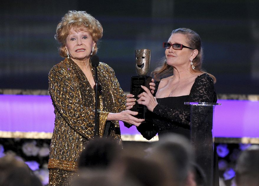 "In this Jan. 25, 2015, file photo, Carrie Fisher, right, presents her mother Debbie Reynolds with the Screen Actors Guild life achievement award at the 21st annual Screen Actors Guild Awards at the Shrine Auditorium in Los Angeles. ""La La Land"" star Ryan Gosling thanked Reynolds at the Palm Springs Film Festival on Monday, Jan. 2, 2017, for serving as an inspiration to the cast and crew of the film. (Photo by Vince Bucci/Invision/AP, File) **FILE**"