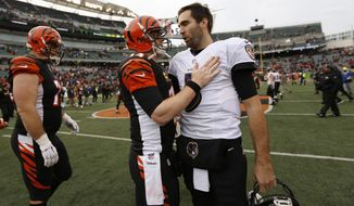 Cincinnati Bengals quarterback Andy Dalton, center left, and Baltimore Ravens quarterback Joe Flacco, center right, meet after an NFL football game, Sunday, Jan. 1, 2017, in Cincinnati. The Bengals won 27-10. (AP Photo/Frank Victores)