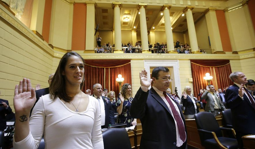 Rhode Island state Rep. Moira Walsh, D-Providence, left, and R.I. Rep. Joseph Shekarchi, D-Warwick, center, take the oath of office, Tuesday, Jan. 3, 2017, during ceremonies in the House Chamber at the Statehouse in Providence, R.I. One of the most lopsided Democratic-controlled legislatures in the country opened its 2017 session with the swearing-in of lawmakers and the election of a House speaker and Senate president Tuesday. (AP Photo/Steven Senne)