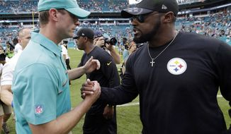 FILE - In this Oct. 16, 2016, file photo, Miami Dolphins head coach Adam Gase, left, greets Pittsburgh Steelers head coach Mike Tomlin, after an NFL football game in Miami Gardens, Fla. Miami's 30-15 drumming of Pittsburgh in mid-October sapped the Steelers of their early season swagger. It also started a painful but necessary process of rethinking how they do things on the fly. A rematch awaits in the wild card round on Sunday. (AP Photo/Wilfredo Lee, File0