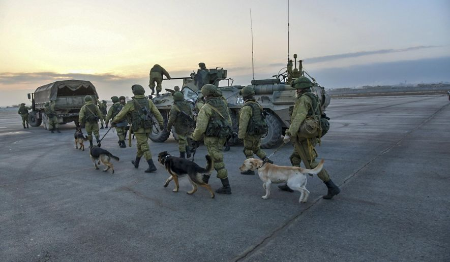 This undated handout photo released by the Russian Defense Ministry claims to show Russian Military engineers with sniffing dogs walking towards their APCs to operate in Aleppo, Syria. (Russian Defense Ministry Press Service photo via AP)