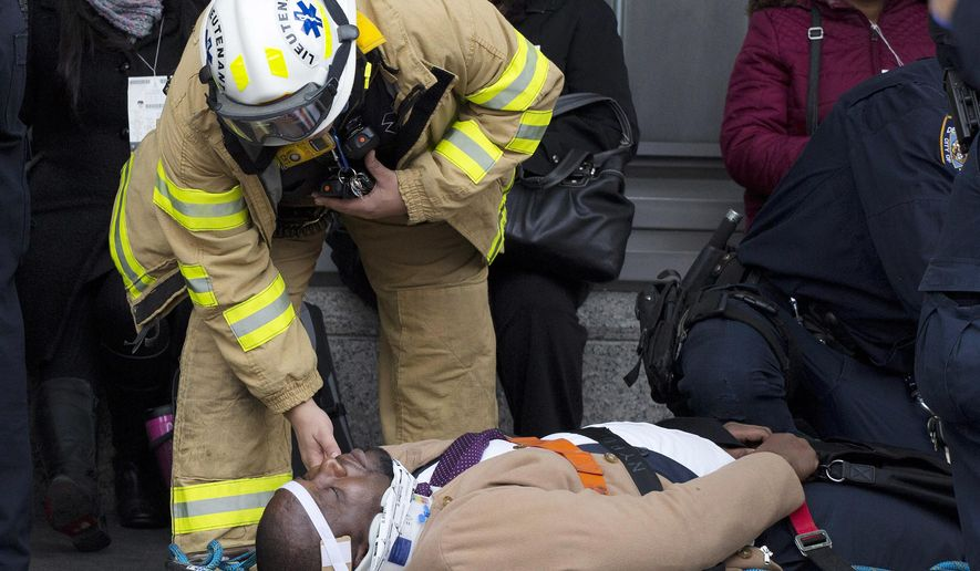 An injured passenger is assisted by an EMS worker as he lies on a gurney outside Atlantic Terminal after a Long Island Rail Road incident, Wednesday, Jan. 4, 2017, in the Brooklyn borough of New York. Officials said a commuter train either hit something or derailed as it arrived at the terminal. (AP Photo/Mark Lennihan)