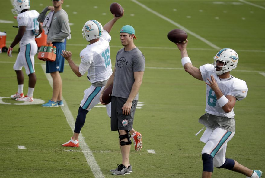 Miami Dolphins quarterback Ryan Tannehill, center, watches as quarterbacks T.J. Yates (16) and Matt Moore (8) throw during NFL football practice, Wednesday, Jan. 4, 2017 in Davie, Fla. Tannehill didn't take part in practice, making it unlikely he'll return from a left knee injury. The Dolphins play the Pittsburgh Steelers in an AFC Wild-Card game Sunday. (AP Photo/Lynne Sladky)