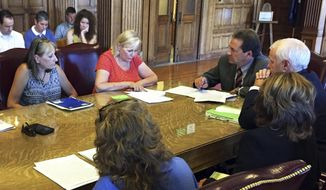 This July 29, 2015 photo shows April Hall, seated at left, whose granddaughter was killed by the mother's boyfriend in June 2011, and Robin Castle, second from left, a licensed clinical professional counselor, during a meeting with Gov. Steve Bullock, seated third from left, to demand improvements in the state Division of Child and Family Services, in Helena, Mont. A review of 14 child deaths in Montana from July 2015 to November 2016 concluded that most died of abuse or neglect, with several common factors that should have raised red flags with child protection workers. (Kristin Inbody/The Great Falls Tribune via AP)