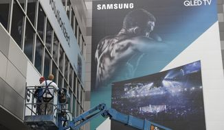 Workers hang up a sign near a Samsung TV banner during setup for CES International, Tuesday, Jan. 3, 2017, in Las Vegas. The show runs from January 5-8. (AP Photo/John Locher)