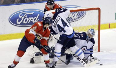 Winnipeg Jets goalie Connor Hellebuyck (37) stops a shot by Florida Panthers center Michael Sgarbossa (48) as Josh Morrissey (44) defends during the first of an NHL hockey game, Wednesday, Jan. 4, 2017, in Sunrise, Fla. (AP Photo/Alan Diaz)