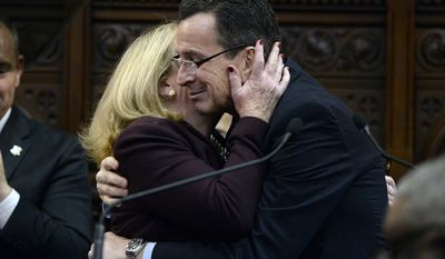 Connecticut Gov. Dannel P. Malloy is embraced by his wife Cathy, left, after delivering the State of the State address during opening session at the state Capitol, Wednesday, Jan. 4, 2017, in Hartford, Conn. (AP Photo/Jessica Hill)