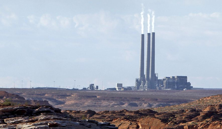 This Sept. 4, 2011, file photo shows the main plant facility at the Navajo Generating Station, as seen from Lake Powell in Page, Ariz. (AP Photo/Ross D. Franklin, File)