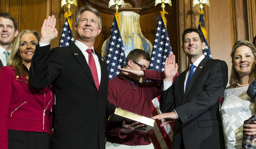House Speaker Paul Ryan of Wis. administers the House oath of office to Rep. Roger Marshall, R-Kan.,during a mock swearing in ceremony on Capitol Hill in Washington, Tuesday, Jan. 3, 2017,  as his son dabs, a pose made popular by NFL quarterback Cam Newton.(AP Photo/Zach Gibson)
