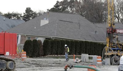 A construction worker walks by a home collapsed by a sinkhole, Wednesday, Jan. 4, 2017, in Fraser, Mich. Officials investigating the sinkhole in Macomb County are examining whether a hole drilled into a sewer line caused the pipe to collapse. County Public Works Commissioner Candice Miller said Wednesday the hole was made during an inspection after a sewer collapse in 1978. The current sinkhole was discovered Dec. 24 in the Detroit suburb of Fraser by the homeowners who awoke to find their house sinking. (AP Photo/Carlos Osorio)