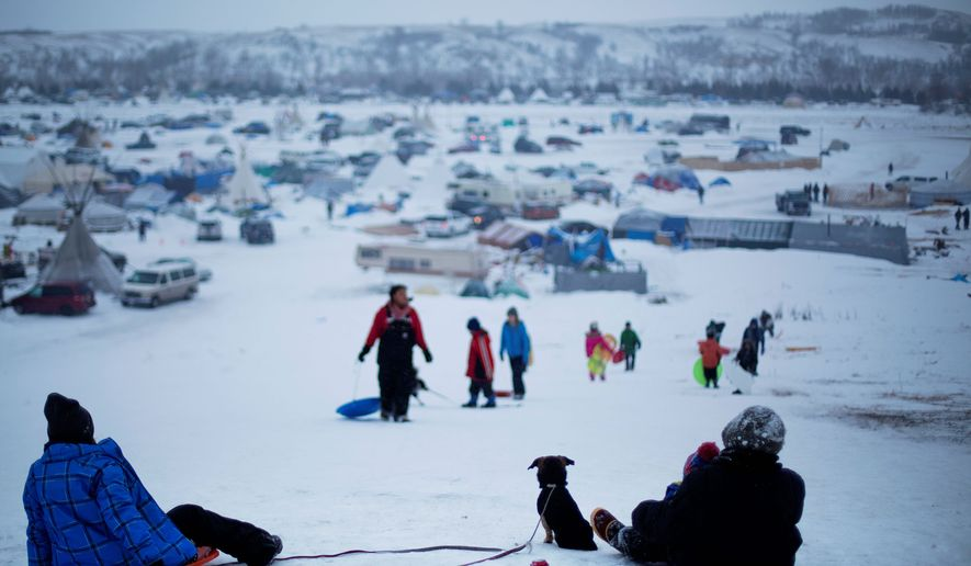 The Oceti Sakowin camp where people have gathered to protest the Dakota Access oil pipeline stands in the background as a children sled down a hill in Cannon Ball, N.D., in this Dec. 1, 2016, file photo. (AP Photo/David Goldman, File) **FILE**
