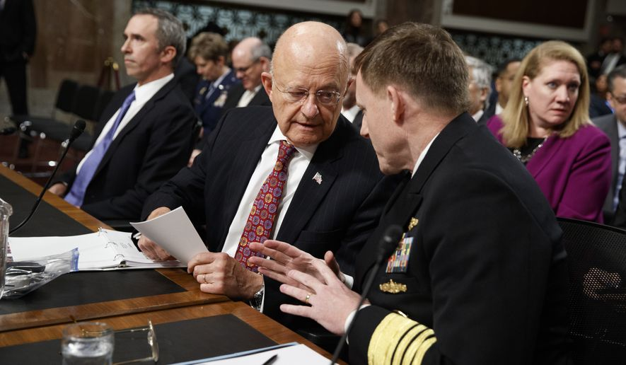 "Director of National Intelligence James Clapper, center, talks with National Security Agency and Cyber Command chief Adm. Michael Rogers, on Capitol Hill in Washington, Thursday, Jan. 5, 2017, prior to testifying before the Senate Armed Services Committee Hearing on ""Foreign Cyber Threats to the United States."" At left is Defense Undersecretary for Intelligence Marcel Lettre II. (AP Photo/Evan Vucci)"