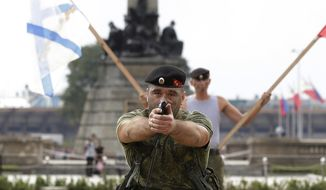 A Russian Marine aims his pistol during a Capability Demonstration at Manila's Rizal Park, Philippines on Thursday, Jan. 5, 2017. Russia is eyeing naval exercises with the Philippines and deployed two navy ships for a goodwill visit to Manila as Moscow moves to expand defense ties with the country. (AP Photo/Aaron Favila)