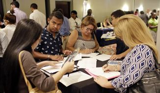 People fill out job applications at a job fair, in Miami Lakes, Fla., in this In a  July 19, 2016, file photo. (AP Photo/Lynne Sladky, File)
