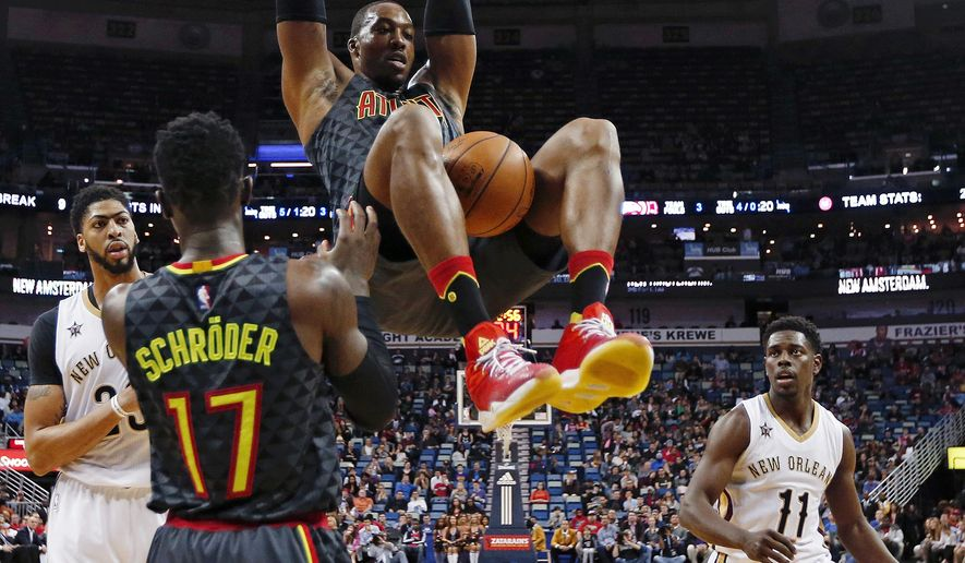Atlanta Hawks center Dwight Howard, top, slam dunks between New Orleans Pelicans forward Anthony Davis and guard Jrue Holiday (11) in the first half of an NBA basketball game in New Orleans, Thursday, Jan. 5, 2017. (AP Photo/Gerald Herbert)