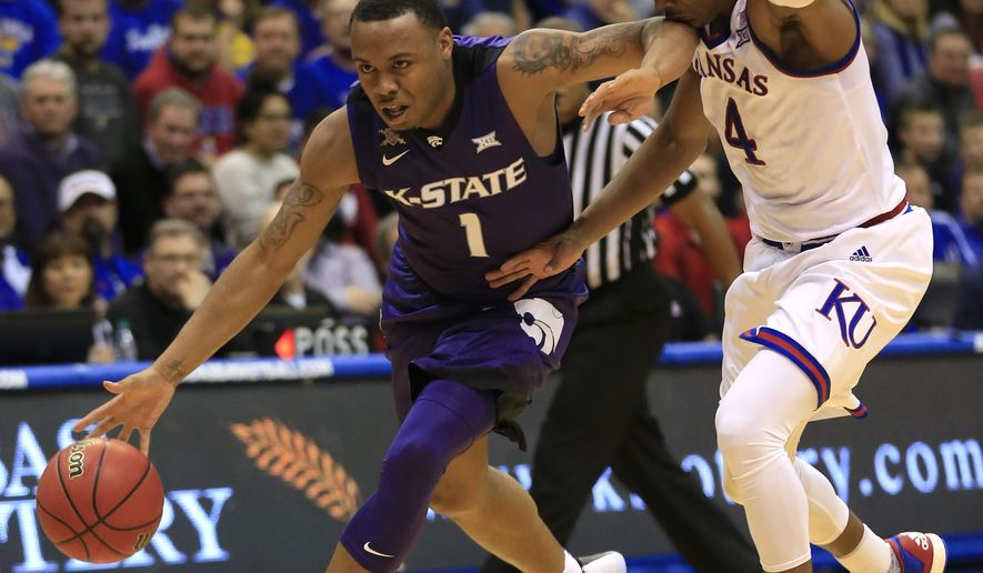 Kansas guard Devonte' Graham (4) catches an elbow to the chin while covering Kansas State guard Carlbe Ervin II (1) during the second half of an NCAA college basketball game in Lawrence, Kan., Tuesday, Jan. 3, 2017. Kansas defeated Kansas State 90-88. (AP Photo/Orlin Wagner)