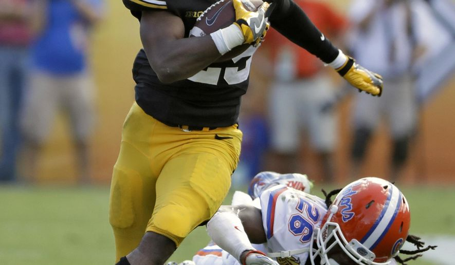 Iowa running back Akrum Wadley (25) gets past Florida defensive back Marcell Harris (26) on a run during the first half of the Outback Bowl NCAA college football game Monday, Jan. 2, 2017, in Tampa, Fla. (AP Photo/Chris O'Meara)