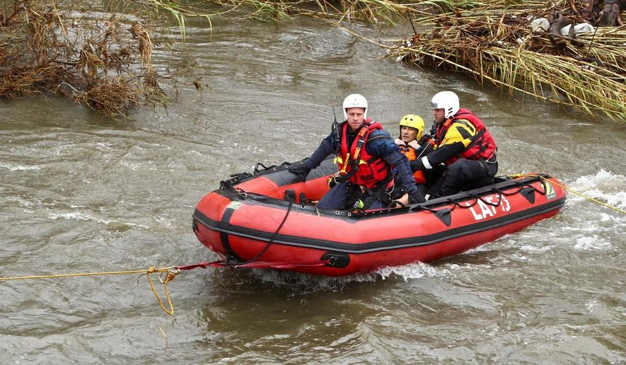 Members of the County of Los Angeles Fire Department Swiftwater Rescue Team rescues a man, center, from flood waters in the Los Angeles River Thursday, Jan . 5, 2017. A California storm has moved on from the soggy north to the desperately dry south, which has seen hardly a drop in recent weeks. Flash flood watches and warnings were issued for areas up and down the state, especially those where brushfires had denuded hillsides and mountain slopes. (Matt Hartman via AP)