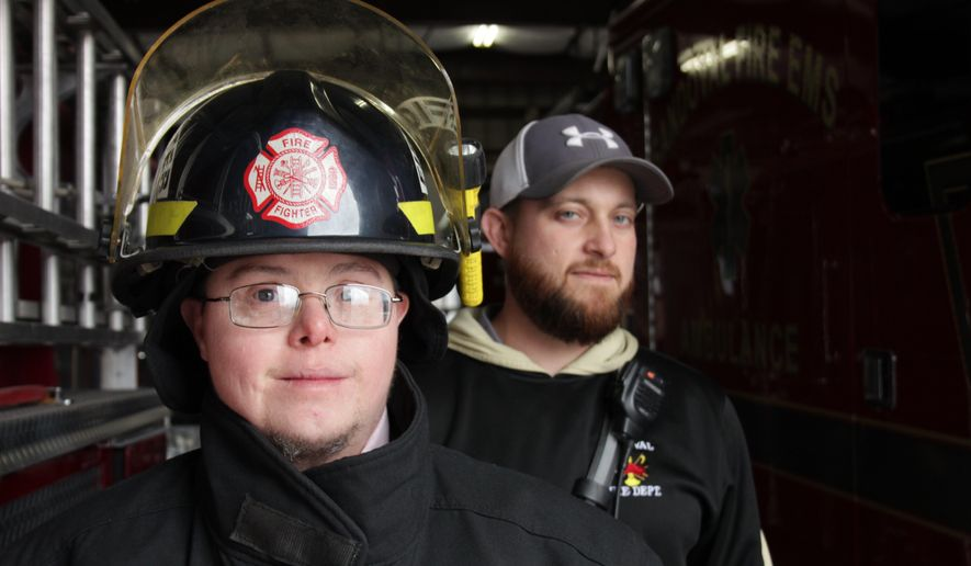 ADVANCE FOR USE SUNDAY, JAN. 8, 2017 AND THEREAFTER - In this Dec. 15,  2016 photo, Sandoval firefighter Jason Eagan, left, poses for a photo with Lt. Matt Horn at the firehouse in Sandoval, Ill. Jason, who is 33, has Down syndrome. There was concern in the department about Jason joining the force but he passed the firefighters' physical, paperwork was filled out, and it became official: Jason was a firefighter. He serves under cadet guidelines, and doesn't go into burning buildings or or engage in perilous rescues. But he is a firefighter. ( Brian Brueggemann/Belleville News-Democrat, via AP)