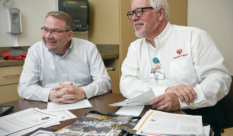 In this Monday, Dec. 19, 2016 photo Joel Vogel and Pete Olson talk about the Mended Hearts volunteer program at the St. Cloud Hospital, in St. Cloud Minn. (Jason Wachter/St. Cloud Times via AP)