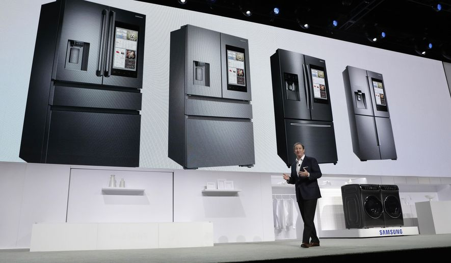 John Herrington, senior vice president of Samsung Electronics America, unveils new refrigerators with Family Hub 2.0 during a Samsung news conference before CES International, Wednesday, Jan. 4, 2017, in Las Vegas. Family Hub 2.0 features an interface on the refrigerator with apps that can be controlled by voice recognition. (AP Photo/John Locher)