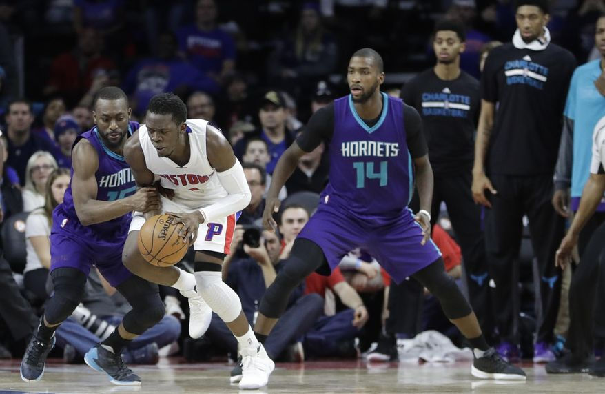 Charlotte Hornets guard Kemba Walker, left, fouls Detroit Pistons guard Reggie Jackson in the closing seconds of the second half of an NBA basketball game, Thursday, Jan. 5, 2017, in Auburn Hills, Mich. (AP Photo/Carlos Osorio)
