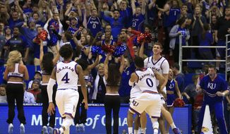Kansas players Devonte' Graham (4) and Frank Mason III (0) celebrate with teammate Kansas guard Sviatoslav Mykhailiuk, right, following an NCAA college basketball game against Kansas State in Lawrence, Kan., Tuesday, Jan. 3, 2017. Mykhailiuk made a last second basket to win the game. Kansas defeated Kansas State 90-88. (AP Photo/Orlin Wagner)