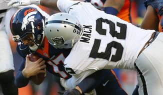 FILE - In this Dec. 13, 2015 file photo, Denver Broncos quarterback Brock Osweiler (17) is sacked by Oakland Raiders defensive end Khalil Mack (52) during the second half of an NFL football game in Denver. For as many similarities as there are between Jadeveon Clowney and Khalil Mack as the two edge defenders taken in the top five of the 2014 draft, there are the stark differences as well. (AP Photo/Joe Mahoney, File)