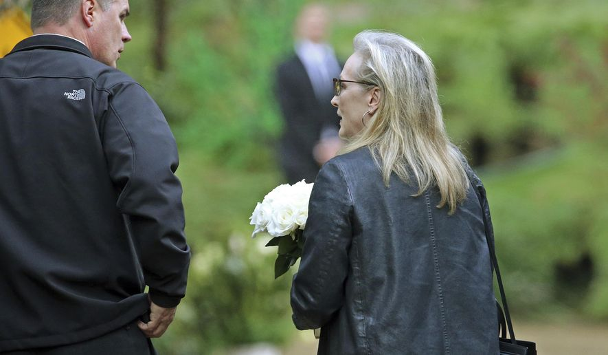 "Actress Meryl Streep arrives with flowers at a memorial service at the homes of Debbie Reynolds and her daughter Carrie Fisher in Los Angeles Thursday, Jan. 5, 2017. Reynolds died Dec. 28 at the age of 84, a day after her daughter died at the age of 60. Streep starred in the film, ""Postcards From the Edge,"" based on Fisher's 1987 semi-autobiographical novel of the same title. (AP Photo/Reed Saxon)"
