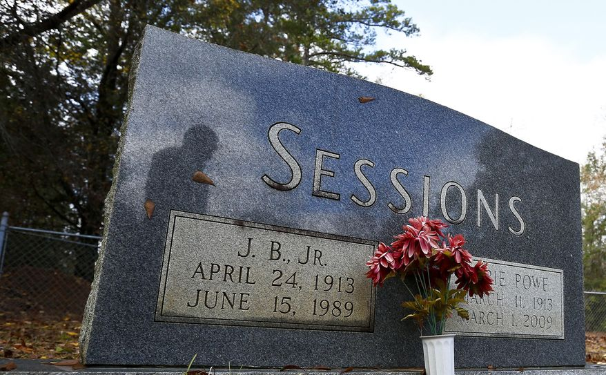 In this photo taken Dec. 6, 2016, Les Johnson, 69, of Camden, Ala., a family friend of Attorney General-designate, Sen. Jeff Sessions, R-Ala. is seen in the reflection of Sessions's parents tombstone at the Bell's Landing Presbyterian Church cemetery in Bell's Landing, Ala. (AP Photo/Brynn Anderson)