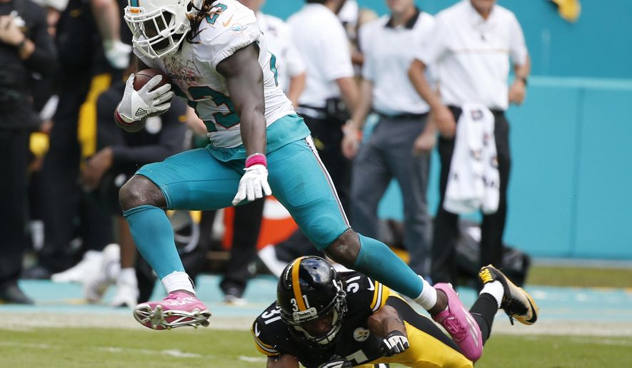 FILE - In this Oct. 16, 2016, file photo, Miami Dolphins running back Jay Ajayi (23) avoids a tackle by Pittsburgh Steelers cornerback Ross Cockrell (31), during the second half of an NFL football game, in Miami Gardens, Fla. This was the first time the Steelers saw Ajayi, and they spent three hours futilely chasing him around in a 30-15 loss. Ajayi is no longer an unknown heading into a rematch in a playoff game on Sunday. (AP Photo/Wilfredo Lee, File)