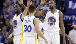 Golden State Warriors' Kevin Durant (35) celebrates with teammates Stephen Curry (30) and Draymond Green (23) after scoring during the first half of an NBA basketball game against the Portland Trail Blazers, Wednesday, Jan. 4, 2017, in Oakland, Calif. (AP Photo/Marcio Jose Sanchez)