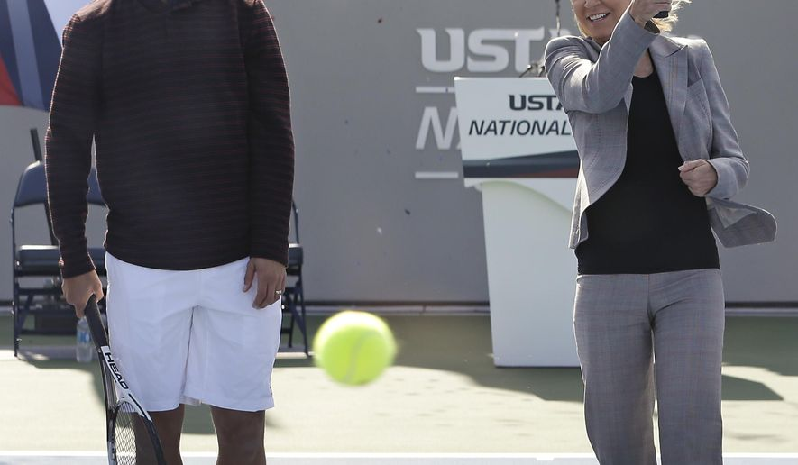 Tennis legend Chris Evert, right, hits a ball as retired tennis star James Blake, left, looks on during the United States Tennis Association grand opening for its new state of the art training facility, Thursday, Jan. 5, 2017, in Orlando, Fla. The USTA is billing the facility as the new home of American tennis, where the best innovation and training will take place. (AP Photo/John Raoux)