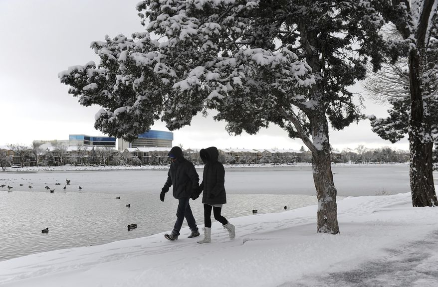 Randy Barr and his girlfriend Jasmina Jordacevic walk along the snowy shore of Virginia Lake Thursday, Jan. 5, 2017, in Reno, Nev. A winter storm has swept aside two long-standing snow records in Boise, Idaho, and is moving east as turbulent weather lined up across much of the country Thursday with watches covering large parts of the South. (Jason Bean/Reno Gazette-Journal via AP)