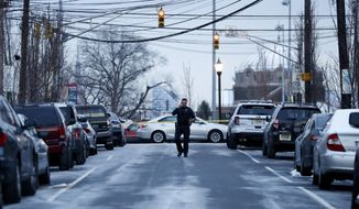 A Union City Police walks inside a police barrier on 20th Street in Union City, N.J., after attention was brought to a home believed to be inhabited by possible family members of the suspect in the shooting at the Fort Lauderdale-Hollywood International Airport, Friday, Jan. 6, 2017, in Union City, N.J. (AP Photo/Julio Cortez)