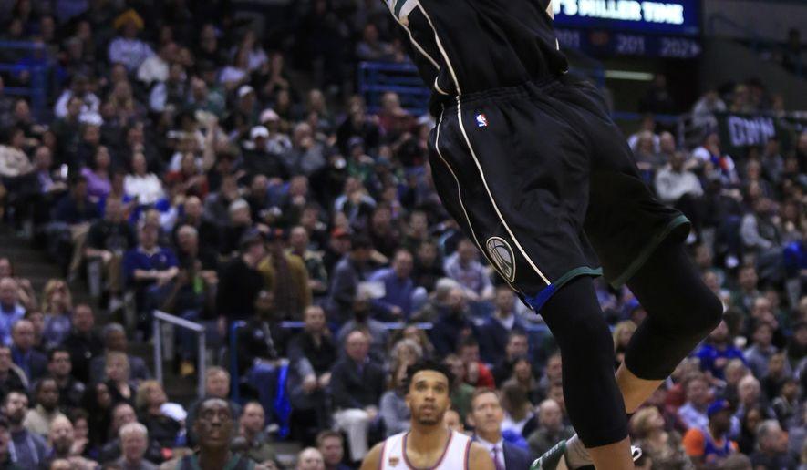 Milwaukee Bucks forward Giannis Antetokounmpo, top, slam-dunks against the New York Knicks during the second half of an NBA basketball game Friday, Jan. 6, 2017, in Milwaukee. (AP Photo/Darren Hauck)
